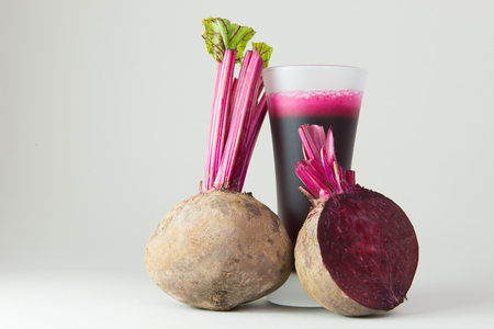 Beet root juice and raw beetroot on white background