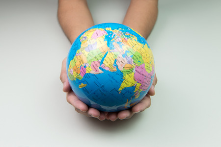 Earth globe in hand over white background
