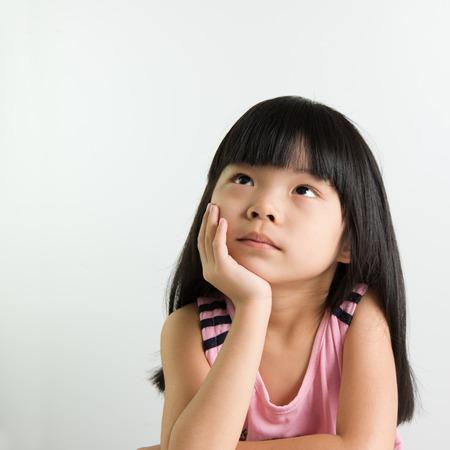 Poco pensamiento Muchacha asiática del niño sobre el fondo blanco