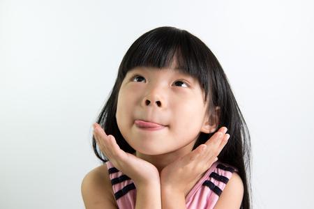 Aziatisch kind toont heerlijke expressie met tong uit