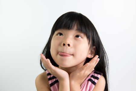 Asian child shows delicious expression with tongue out