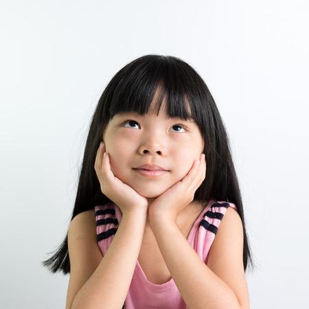 Little Asian girl child thinking over white background