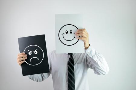 optimismo: El hombre de negocios la celebraci�n de dos documentos con la cara feliz y enojado cada uno de ellos Foto de archivo