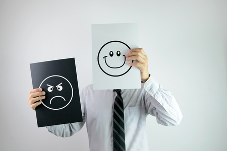 Businessman holding two papers with happy and angry face each on them Archivio Fotografico