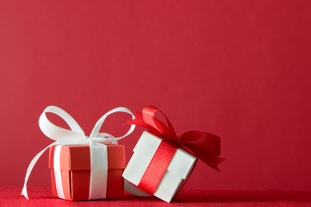 Two gift boxes wrapped with ribbon on red background