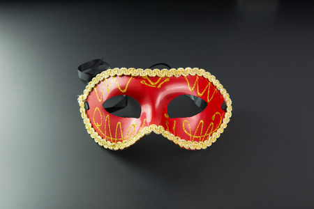 feminine: Red party masquerade mask on dark background Stock Photo
