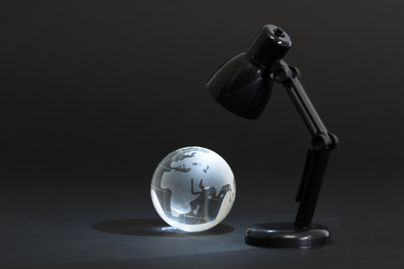 environmental conversation: Table lamp lights up crystal globe in the dark Stock Photo