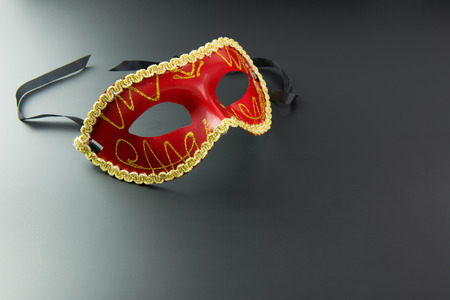 masquerade mask: Red party masquerade mask on dark background Stock Photo