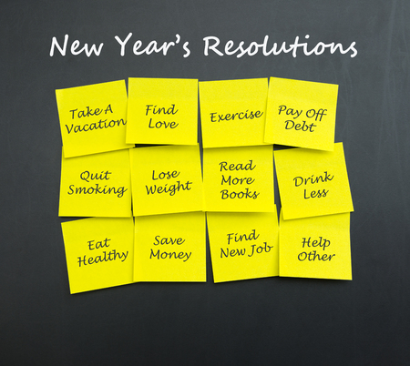 resolutions: Group of new year resolutions post it note on blackboard Stock Photo