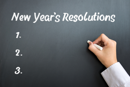 resolutions: The word New year resolutions written on blackboard Stock Photo