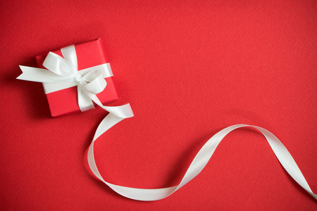 Red gift box with white ribbon isolated on red background