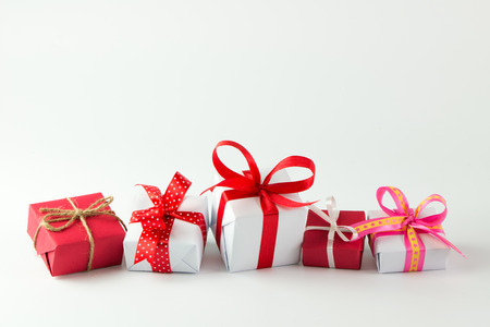 Red and white gift boxes with ribbon in a row isolated on white background