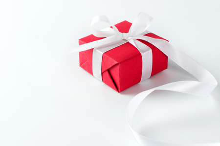 white ribbon: Red gift box with white ribbon isolated on white background