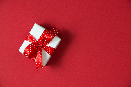 White gift boxes with red ribbon viewed from top isolated on red color background