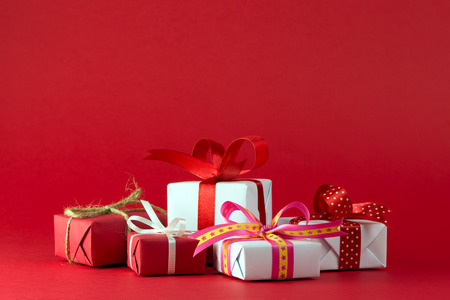 Red and white gift boxes with ribbon isolated on red color background