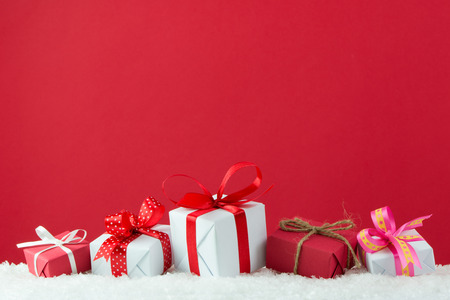 gift packs: Holiday presents with ribbon in a row on snow with red color background Stock Photo