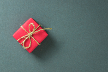 text space: Red gift box on grey background, with copy space