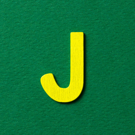 textured: Wooden textured yellow color alphabet J in green background Stock Photo