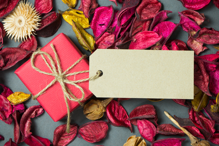 text space: Red gift box with tag on dried petals background Stock Photo