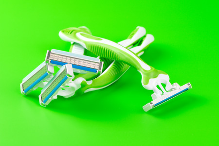 shaver: Close up of two shaving razors on green background