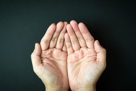 take a: Close up of empty cupped hand, palms up on black background Stock Photo