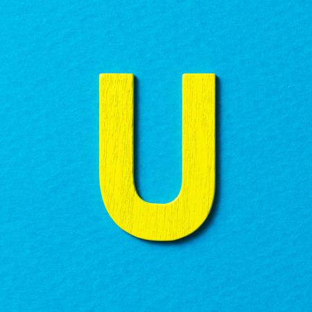color in: Con textura de madera de color amarillo alfabeto U en fondo azul