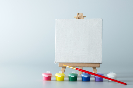 Painting easel with empty canvas and water colors