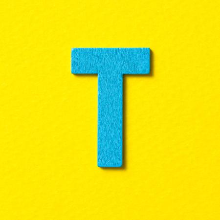 color in: color azul alfabeto de madera con textura T en fondo amarillo