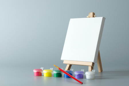 child drawing: Painting easel with empty canvas and water colors
