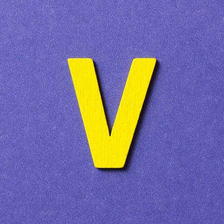 color in: Con textura de madera de color amarillo alfabeto V en el fondo púrpura Foto de archivo