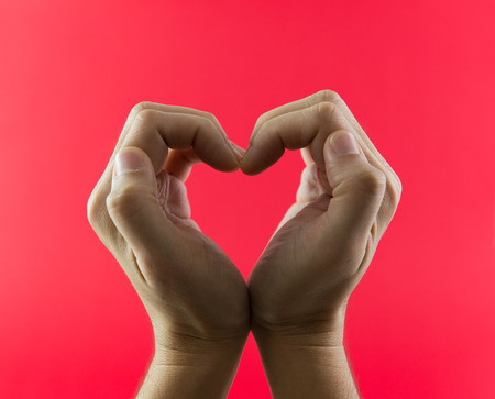 fingerspelling: Hand in heart shape against red color background