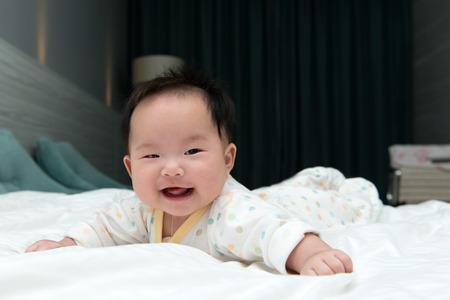 bebe gateando: Beb� sonriente asi�tica que se arrastra en la cama blanca