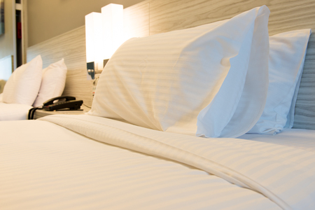 Hotel bedroom with the zoom focus on the pillow 스톡 콘텐츠