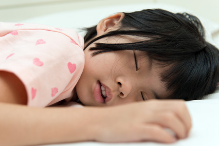 doze: Close up of little Asian girl sleeping soundly Stock Photo