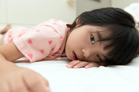 Cierre plano de la niña asiática descansando en la cama Foto de archivo