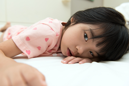 Close up of little Asian girl resting on bed