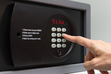 lockbox: Hand press key on black safety box to close