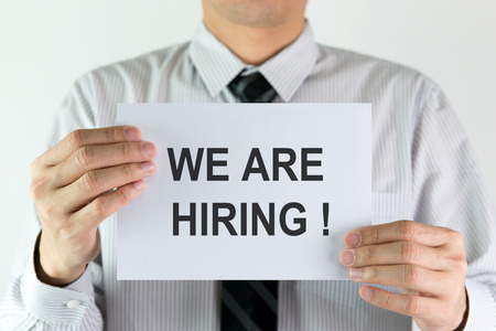 job posting: Businessman in white shirt holding a banner with text we are hiring