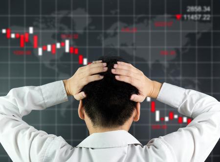 crisis economica: Un inversor está mirando a la pantalla que muestra caída de la bolsa