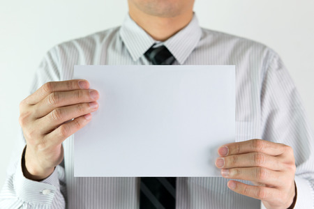 exhibiting: Business man holding a blank sheet of white paper