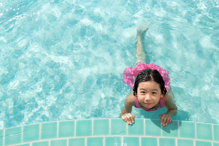 children sport: Asian kid in swimming pool on summer vacation Stock Photo
