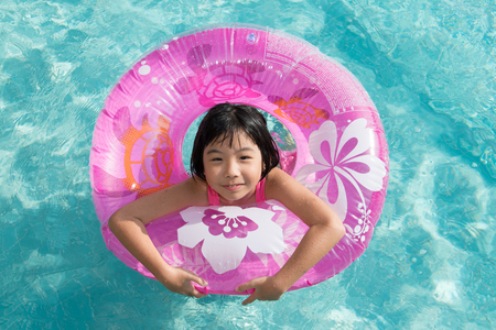 floater: Asian kid in swimming pool on summer vacation Stock Photo