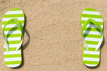 flipflop: Pair of green striped flipflop on beach with copy space