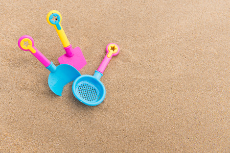 Beach toy set on sand with copy space