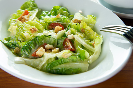 salad bowl: Bowl of Caesar salad with a fork Stock Photo