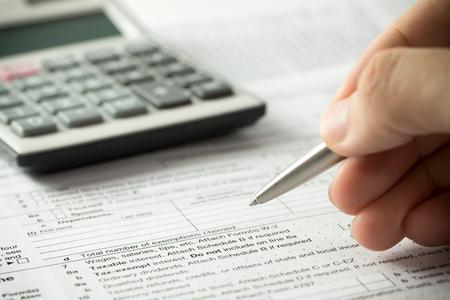 pagando: EEUU individual de impuestos formulario de retorno con lápiz y calculadora