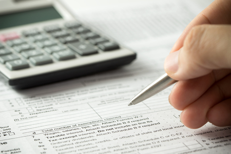 federal tax return: US individual income tax return form with pen and calculator Stock Photo