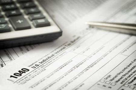 US individual income tax return form with pen and calculator Foto de archivo