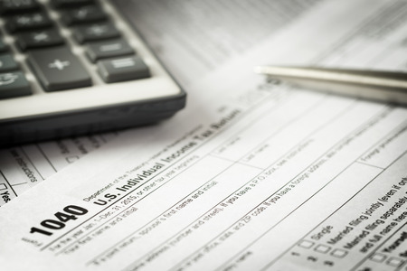 US individual income tax return form with pen and calculator Archivio Fotografico