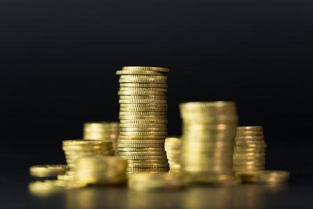 Stos złotych monet na ciemnym tle